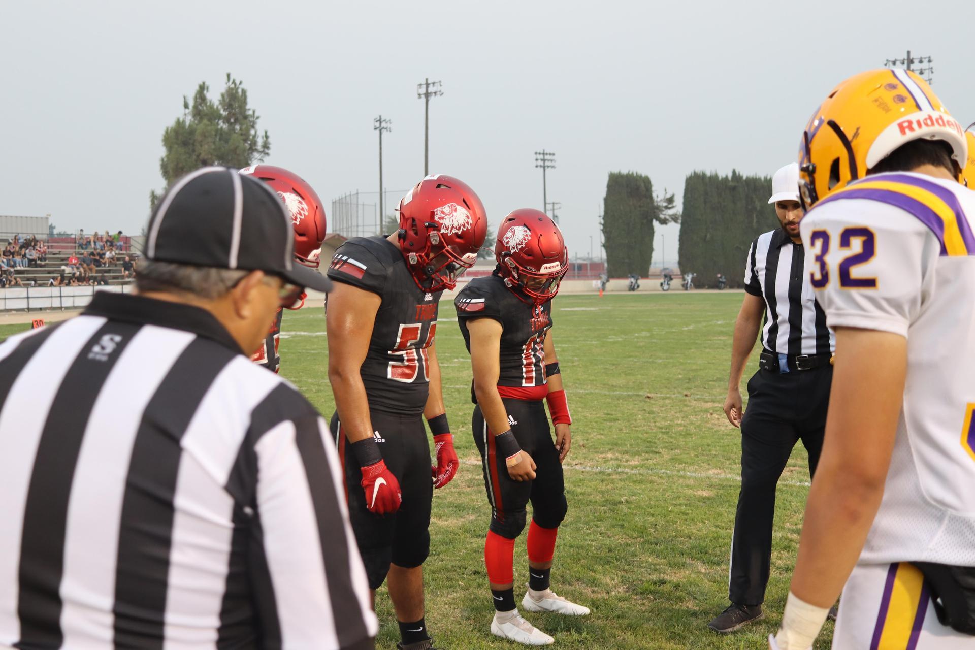 Varsity boys playing football against Lemoore