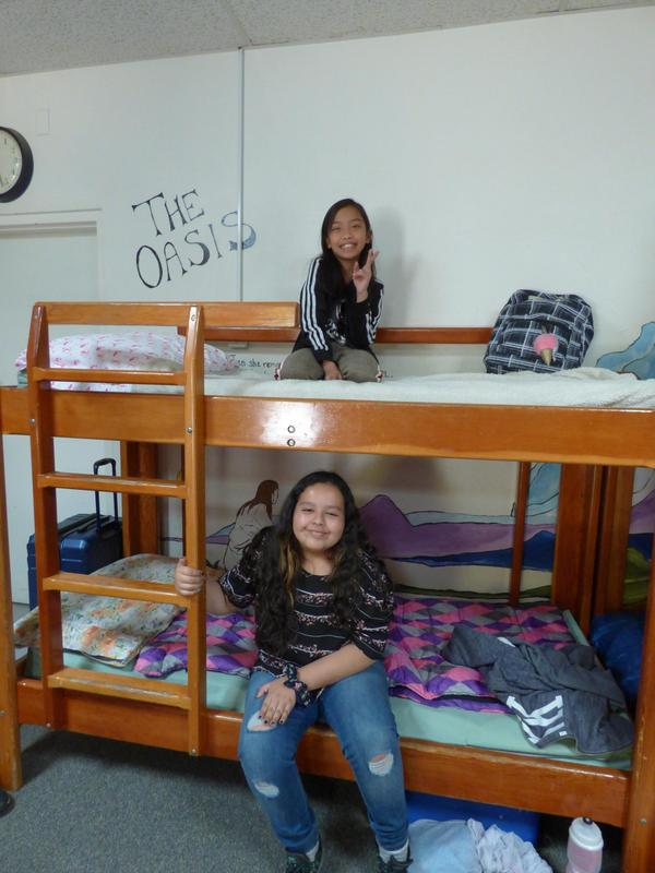 two girls smiling from their bunks in their cabin