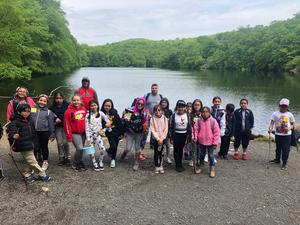 the honor roll kids in front of the lake taking a group picture with their teachers