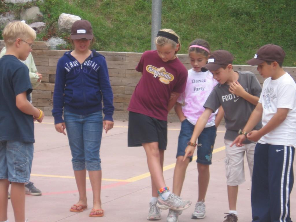 kids point to the ground whilst playing game at camp