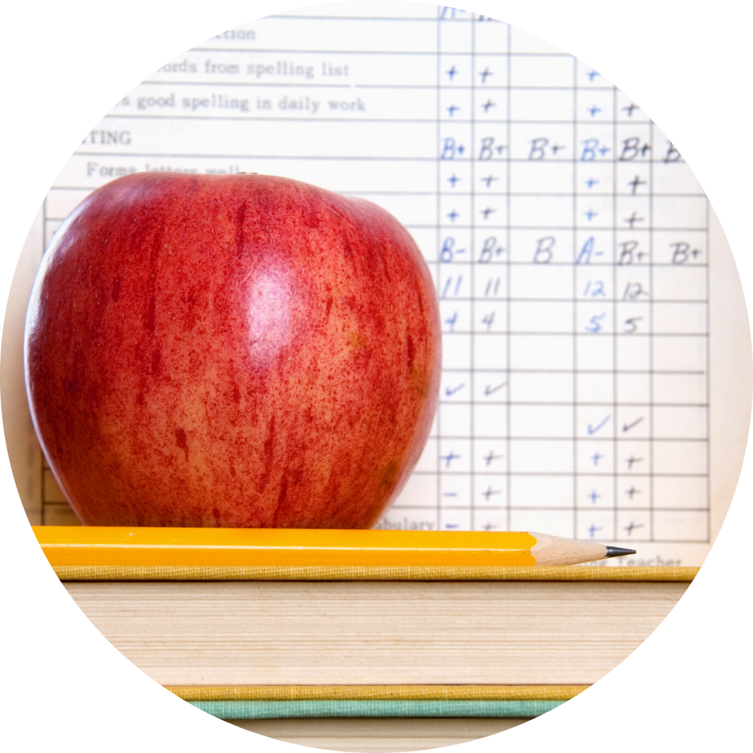 apple on book in front of report card