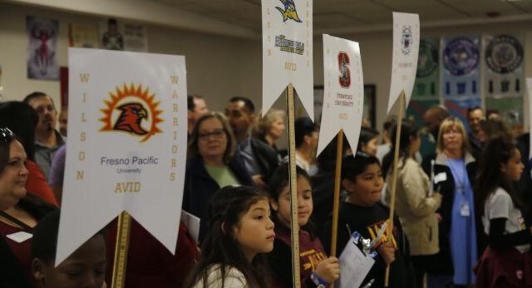 Students with college signs during AVID Showcase.