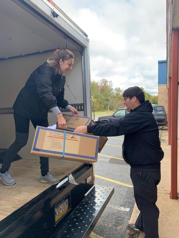 Lady handed a box to a man as they unload the truck full of large boxes of coats for needy student