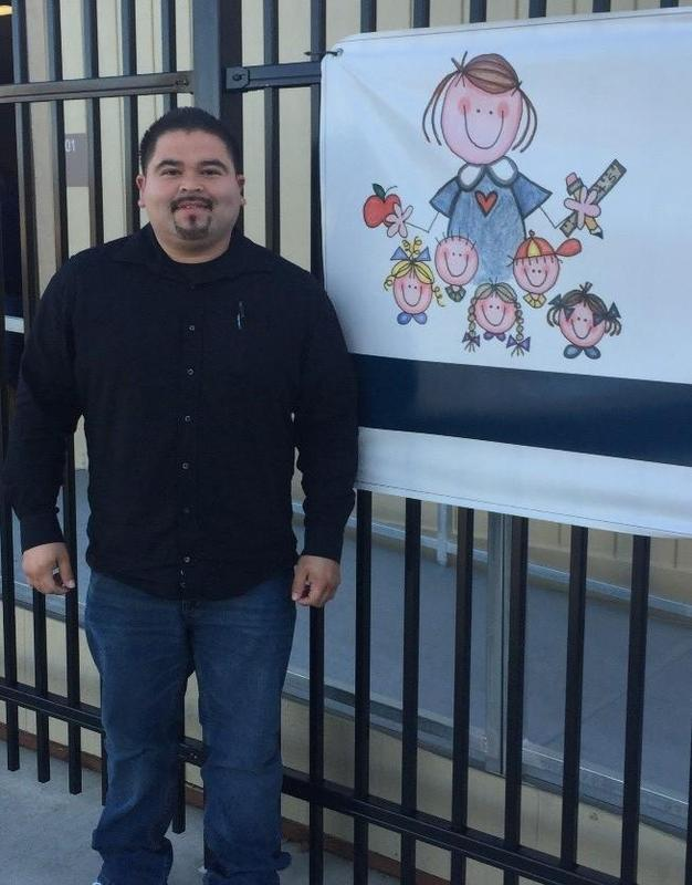 Ruben Grajeda standing in front of a banner with the Hemet Preschool logo.