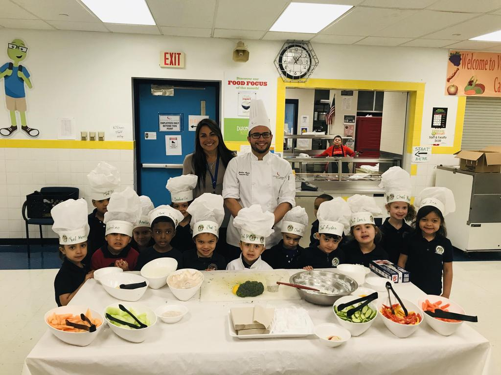 group photo of the pre-k class with their teacher and Chef Josh in front of a table fully of healthy snacks