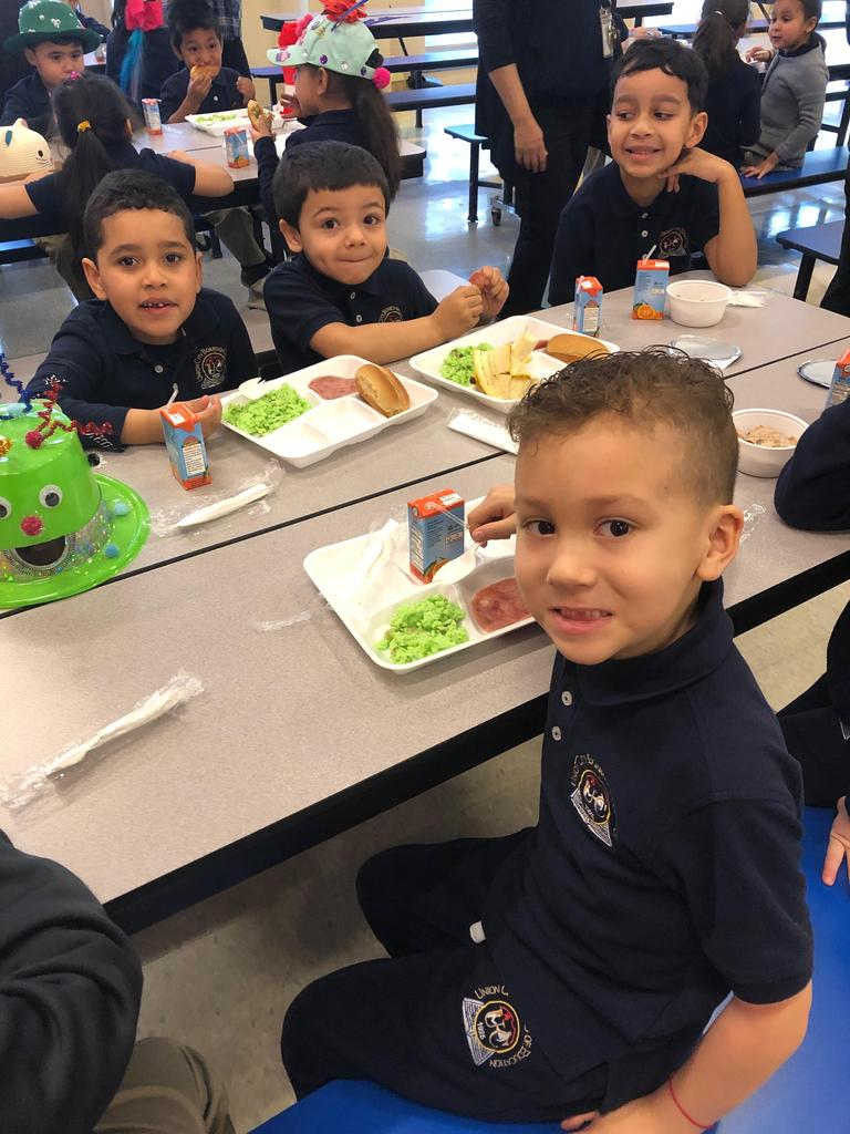 four boys seated at the table eating green eggs and ham
