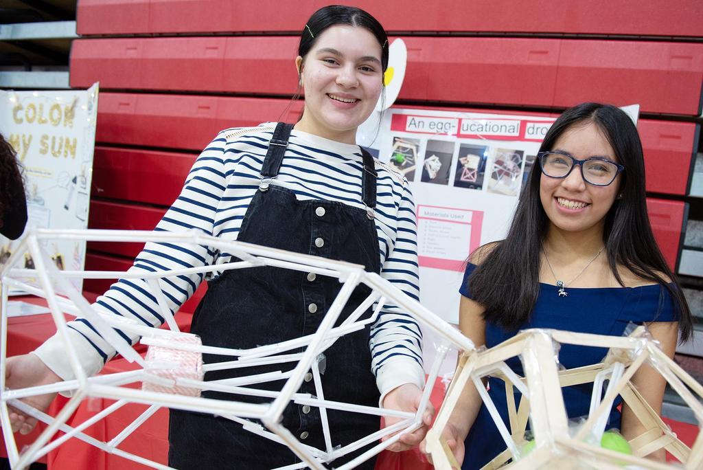 Two female students hold their large and intricate egg-drop devices