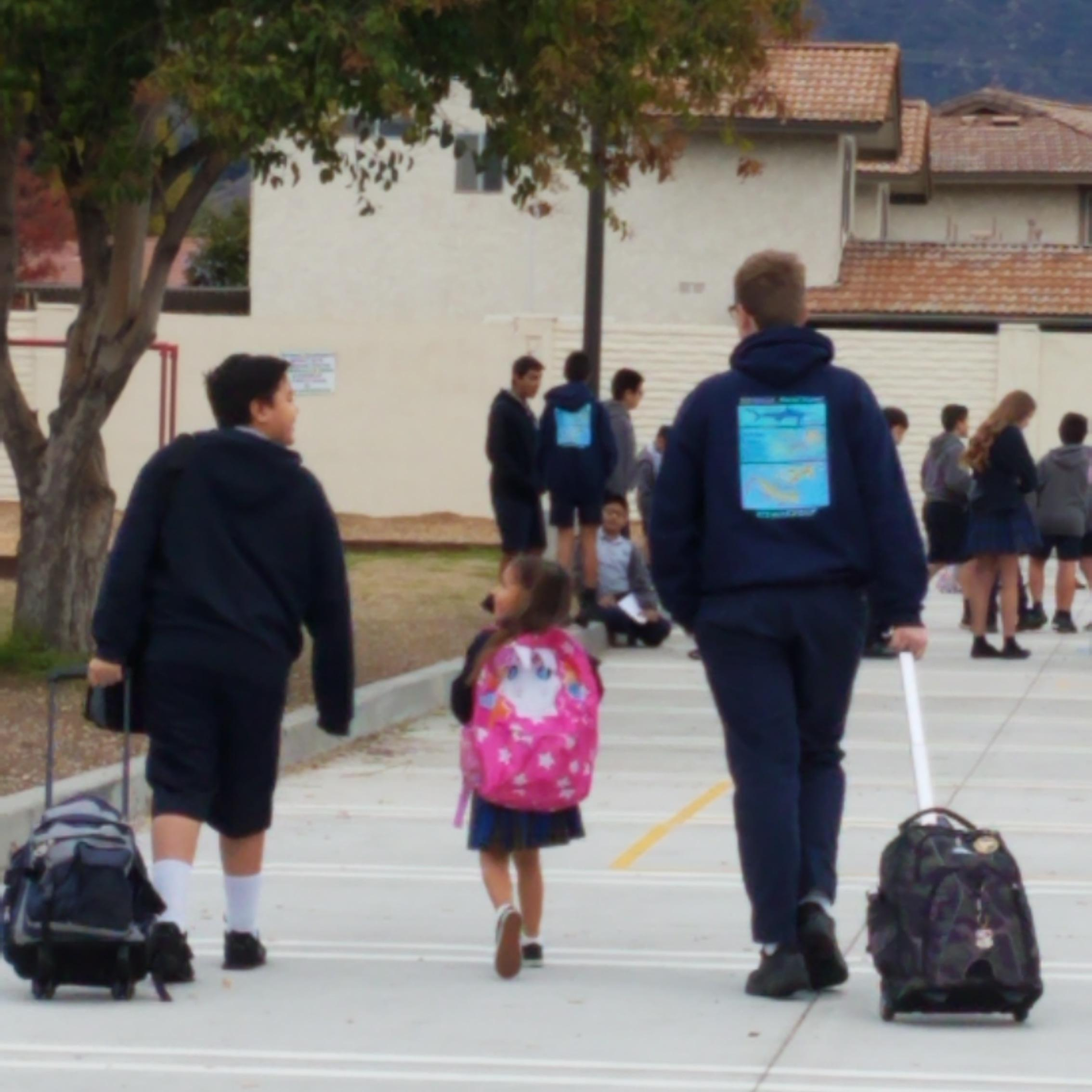 Older students walking a TK student to class