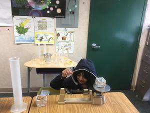 student sitting next to a table with scientific instruments like the triple beam balance and graduated cylinder