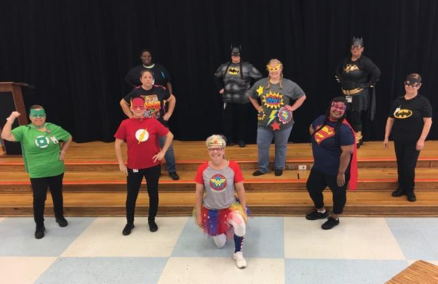 group on stage in superhero shirts