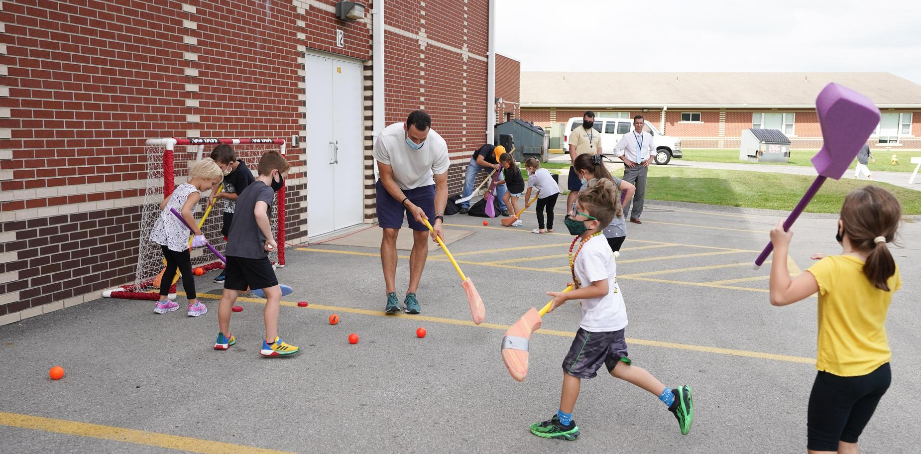 students playing hockey with Brian Dumoulin