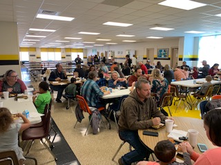Students and adults in cafeteria for a Thanksgiving feast.