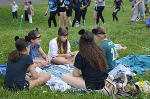 5 girls sitting on a blanket on the grass playing the board game