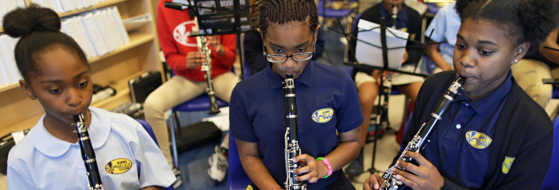 Three KIPP Believe College Prep students playing instruments in music class