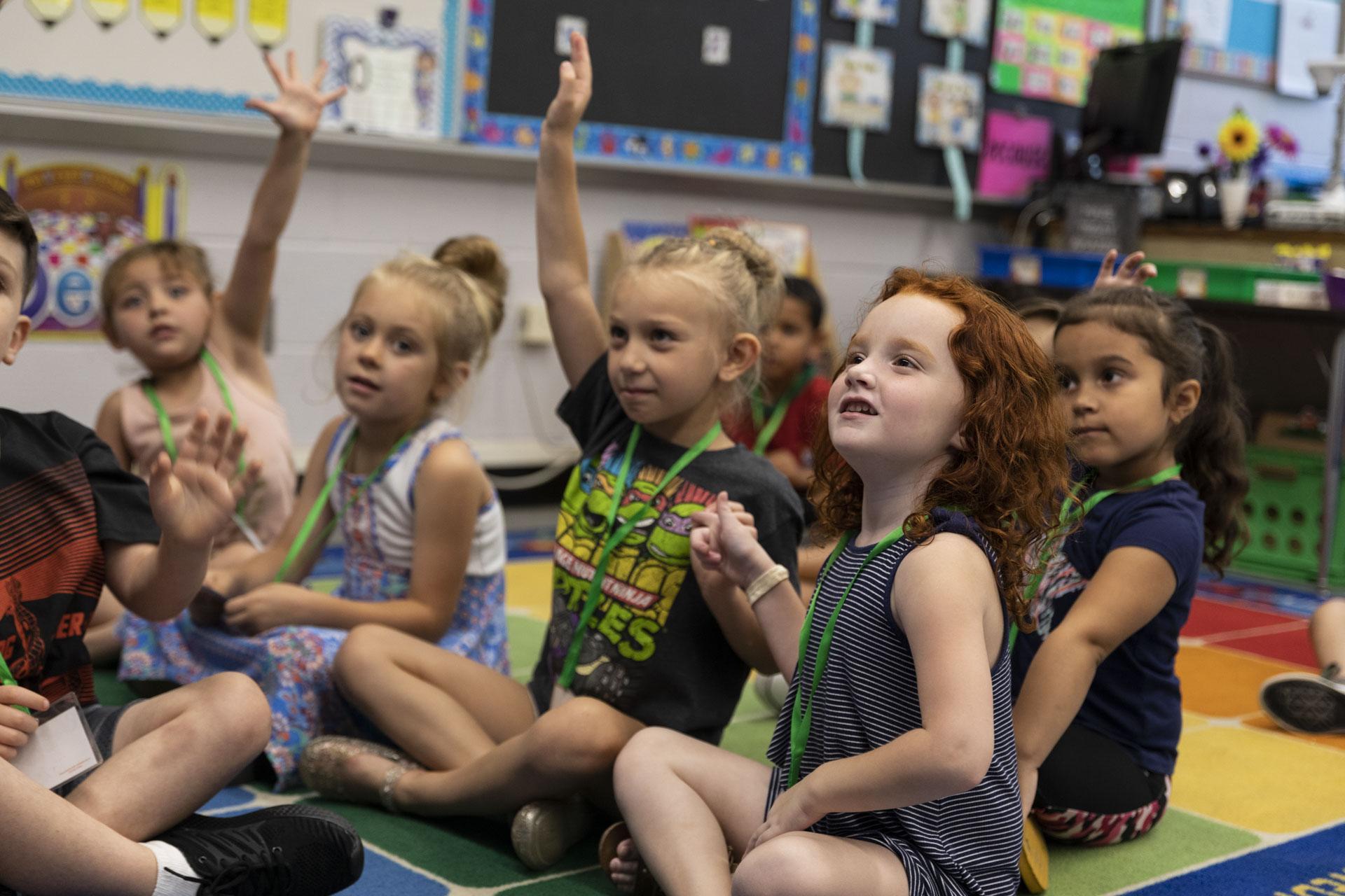 Students sitting on carpet raising hands