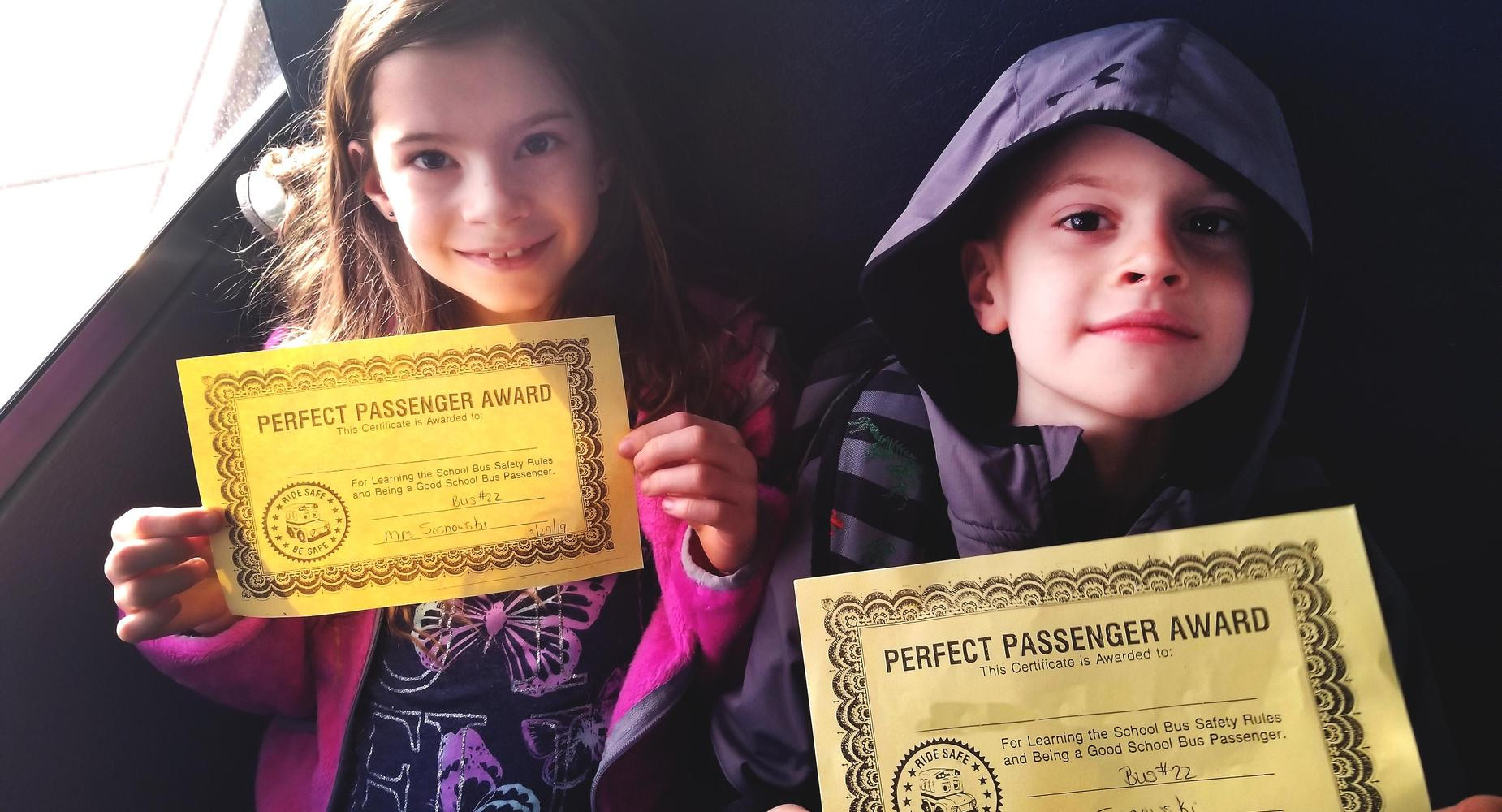 Two students sitting on bus holding award certificate