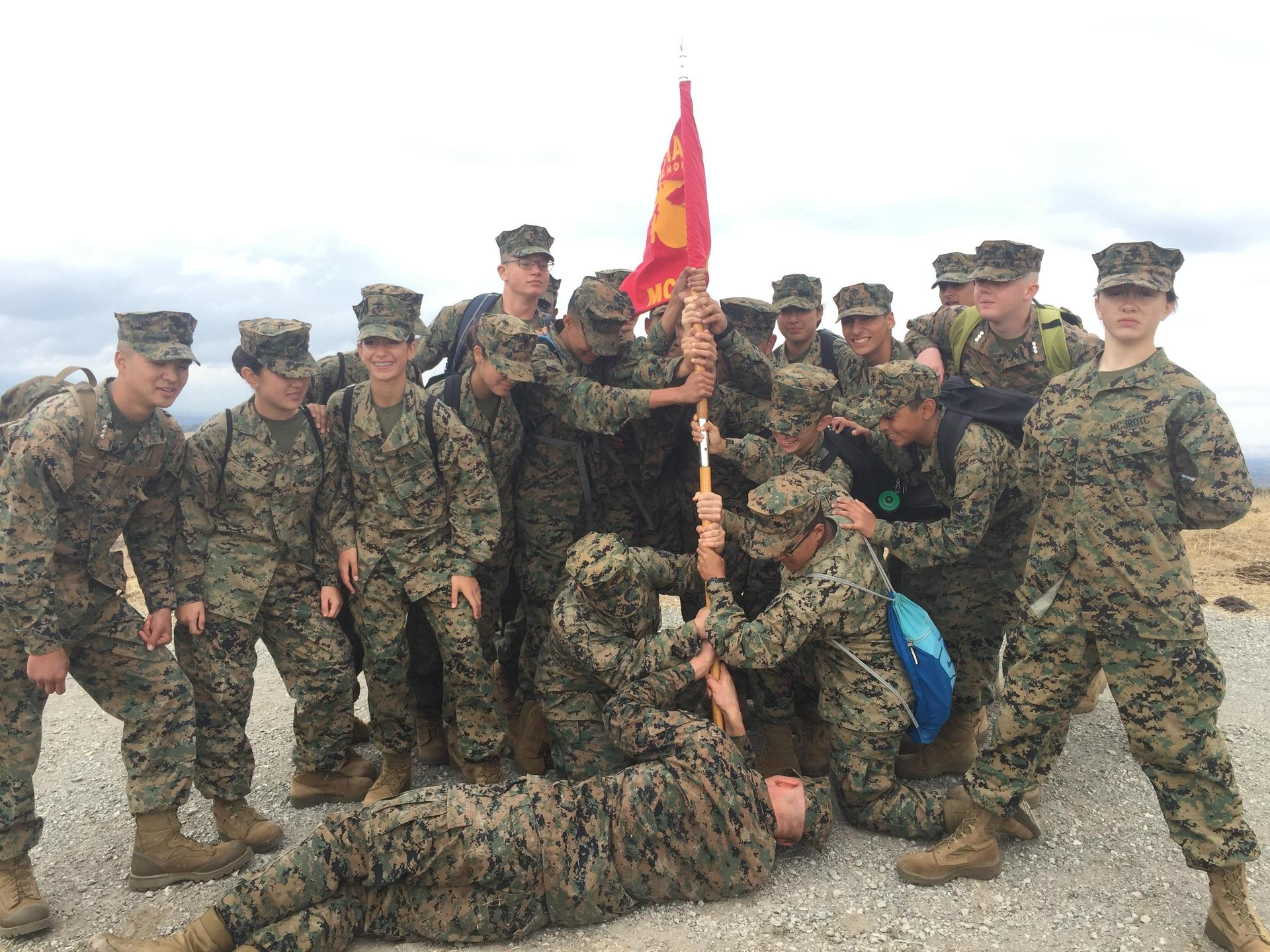 MCJROTC cadets raising Marine Corps flag on top of hill