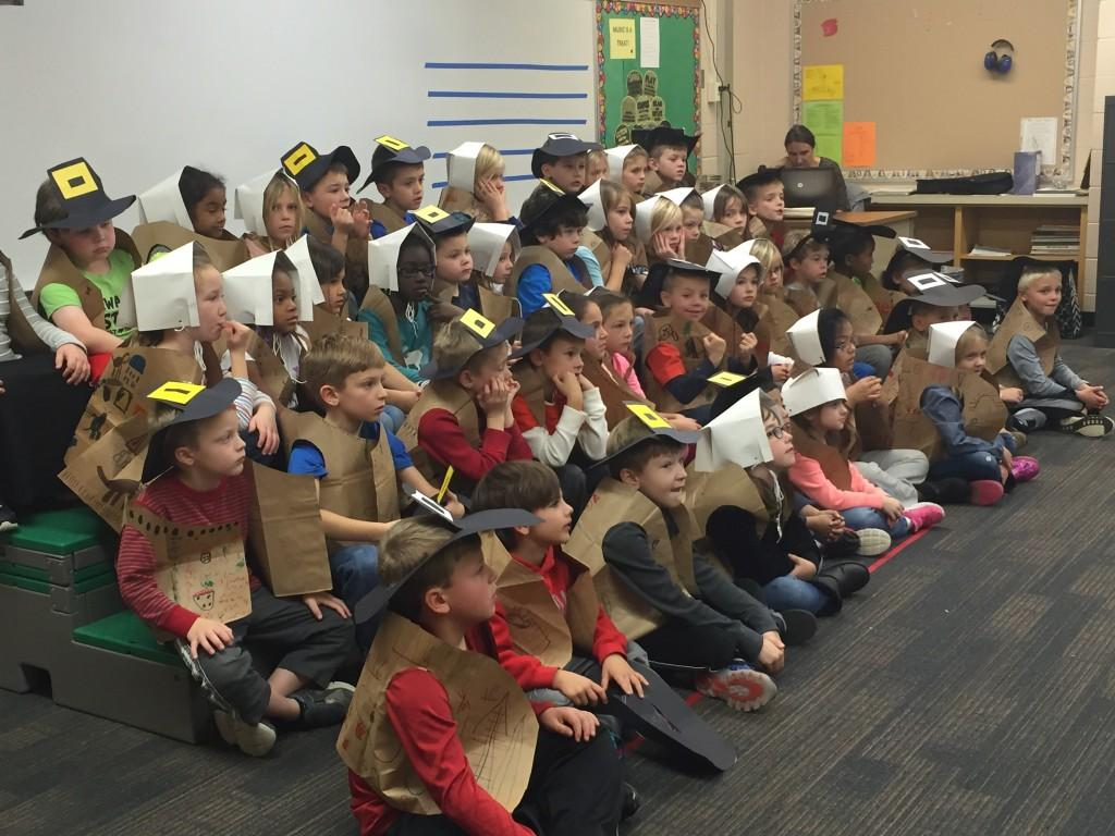 kids sitting in Pilgrim outfits