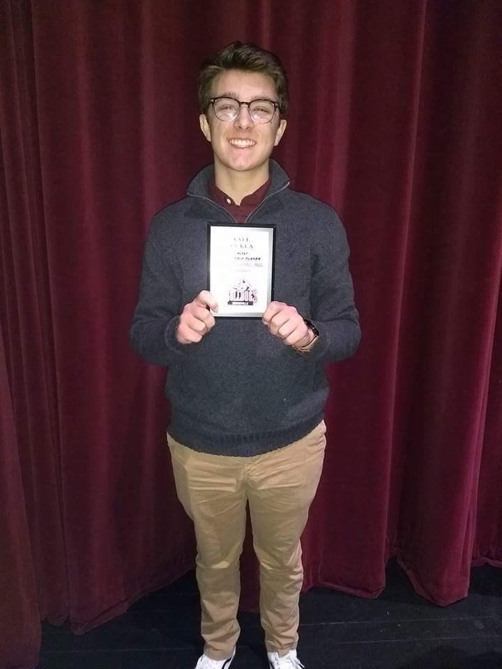 boy holds award
