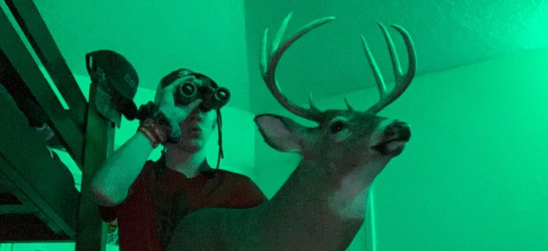 A student holds binoculars and a deer.