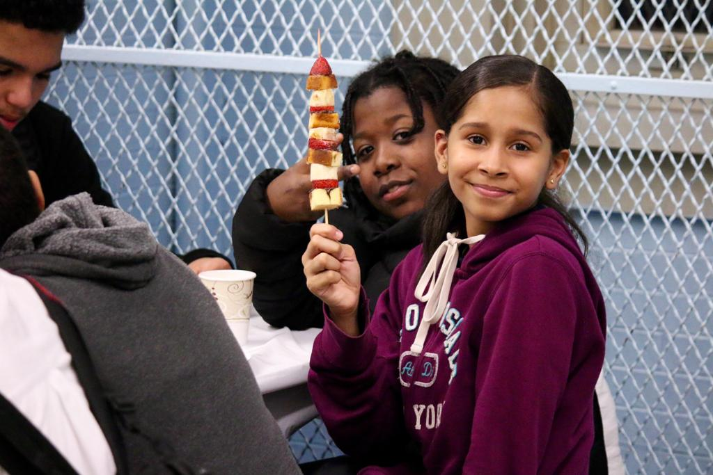 a girl and a boy posing with a desert skewer.