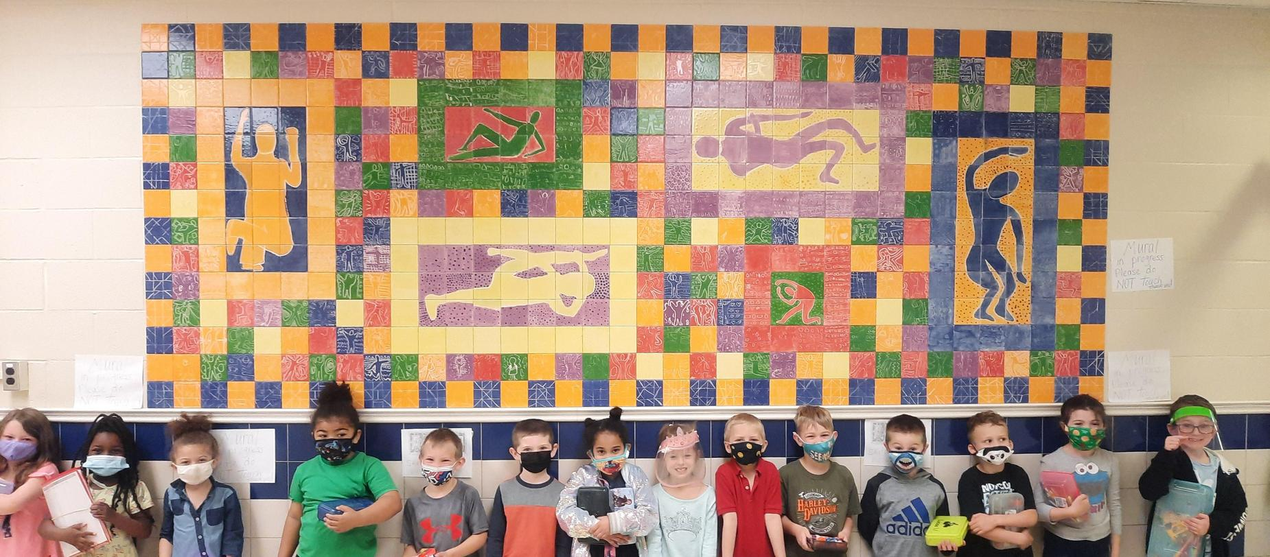 students posing in front of mural