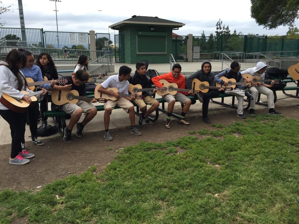 A row of students playing guitar together.