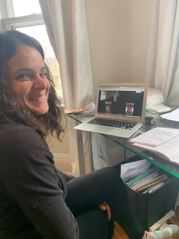 A teacher smiles while teaching online