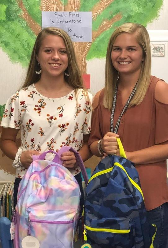 Kensley Chambers presenting PreK book bags to Nikki Stephenson