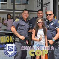 child posing with officers while holding ice cream