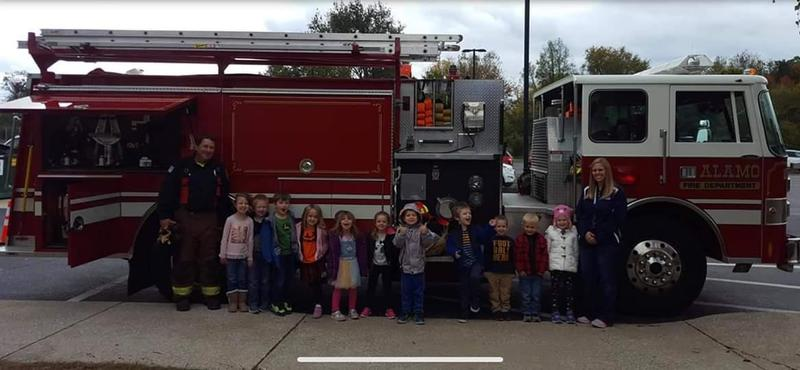 preschool class stands in front of a fire truck