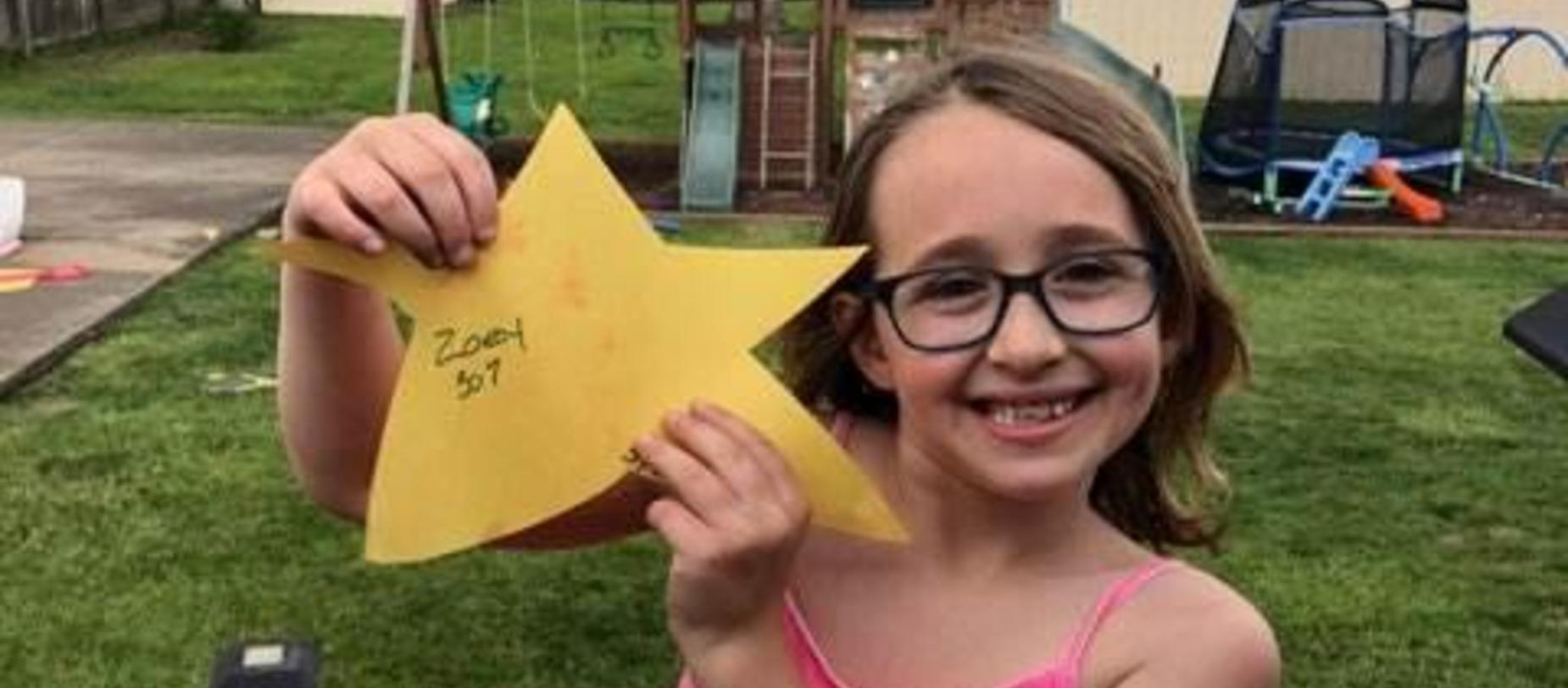 girl smiling for camera holding a gold star