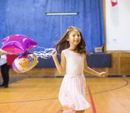 girl receives awards at end of year awards assemblies; seen holding balloons and smiling