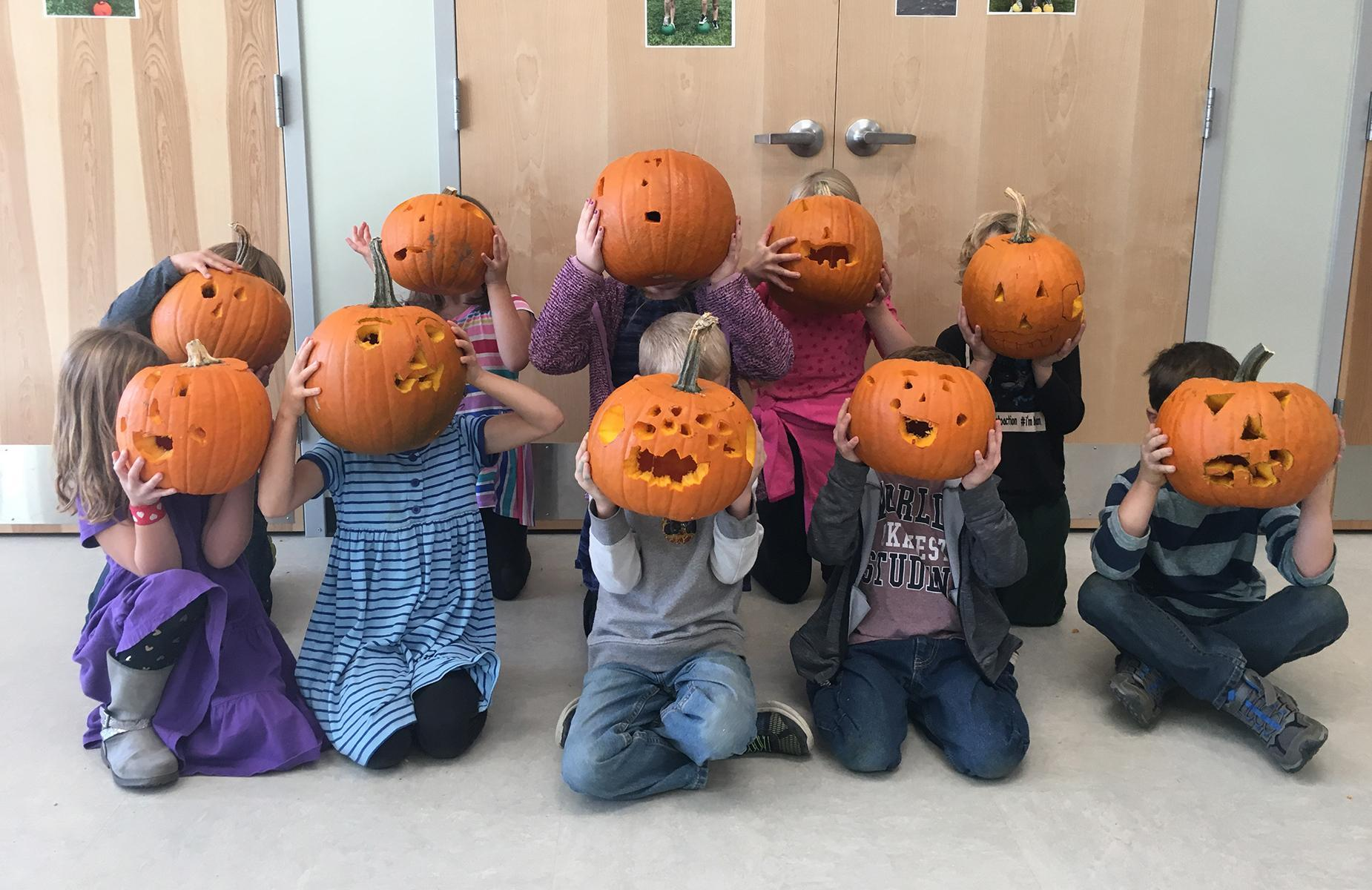 first graders with carved pumpkins