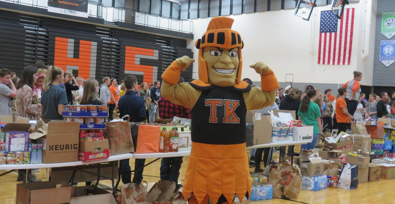 The TKHS Trojan flexes his muscles showing off all the food collected for local food pantries.