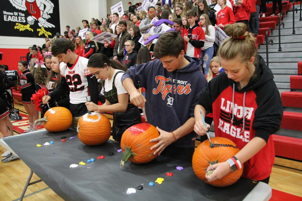 Students painting on pumpkins