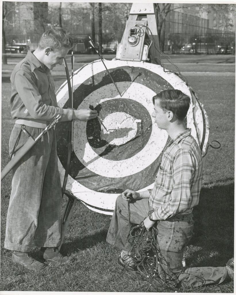 students looking at their arrows in an archary target. Above the target is door bell that rings to assist in tracking the location