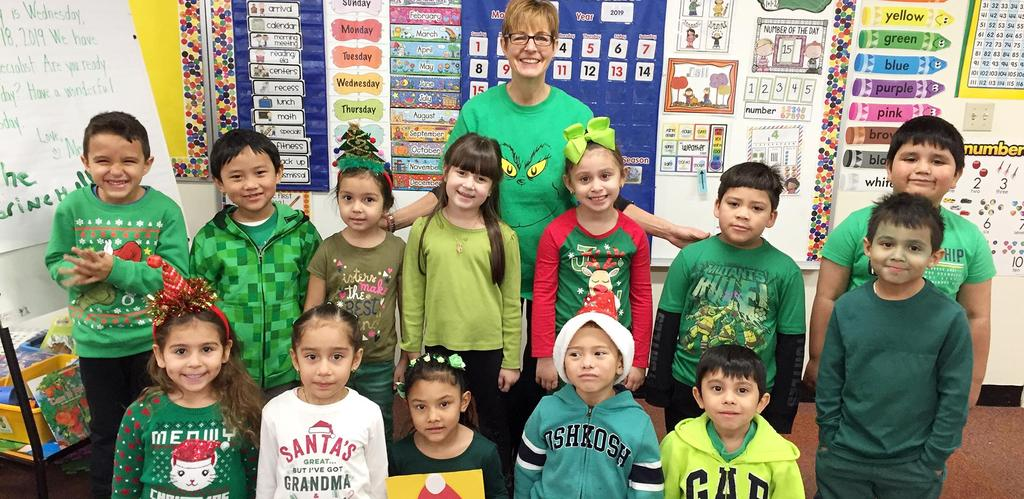 A class of kindergartners wearing green and/or holiday shirts, sweaters, and sweatshirts