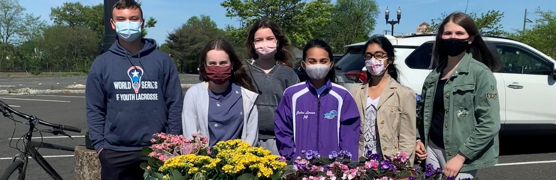 Photo of members of Roosevelt Student Council in front of flowering plants as part of fundraiser.