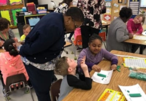 Visitors from the Governor's Office observe students working on math.