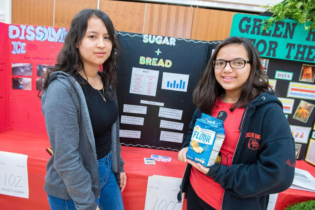 Two students, one holding a bag of flour, stand in front of their project
