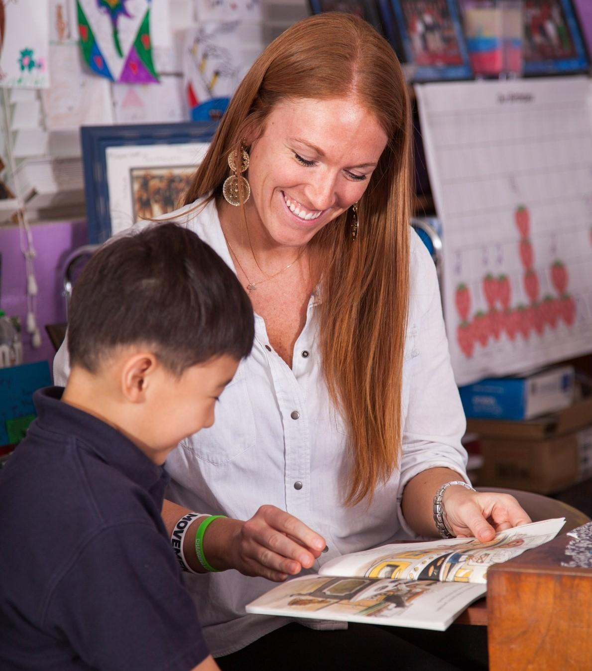 teacher and student smiling as they read a book
