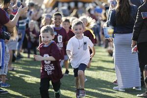 kids in maroon run on field through tunnel of adults