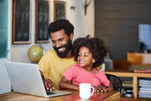 Black father and daughter sitting and looking at a laptop screen