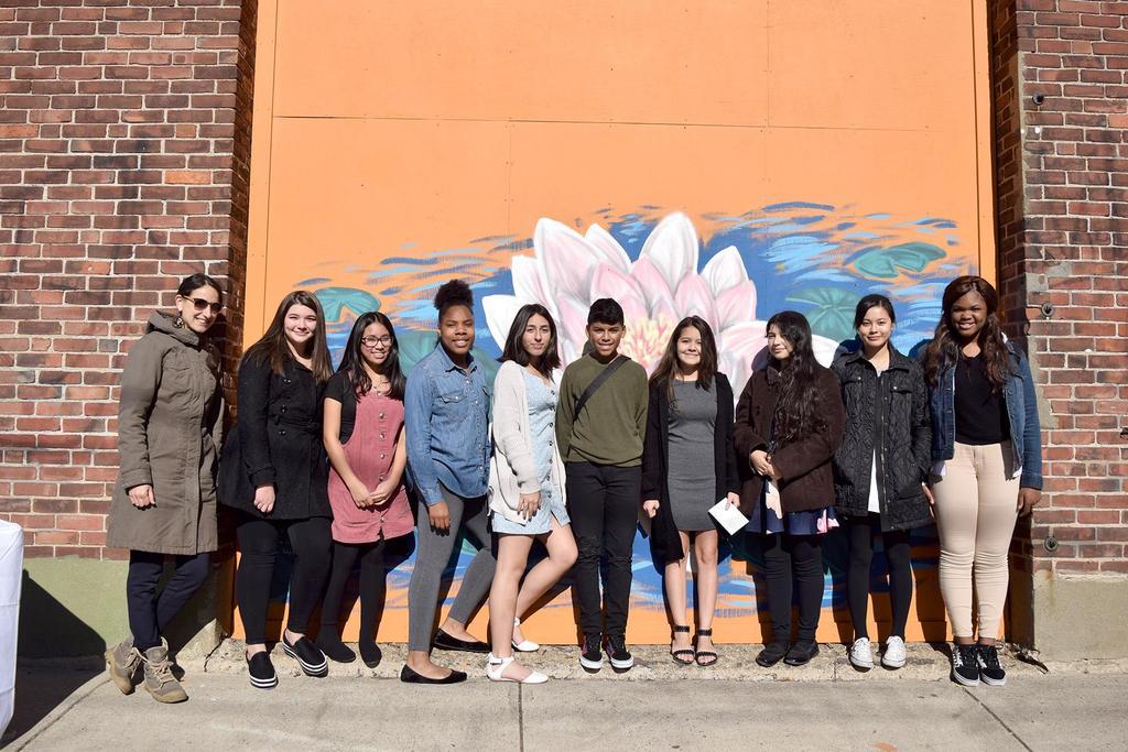 Resident Artist Carolyn Lewenberg and nine EPS students stand in front of the lotus flower mural
