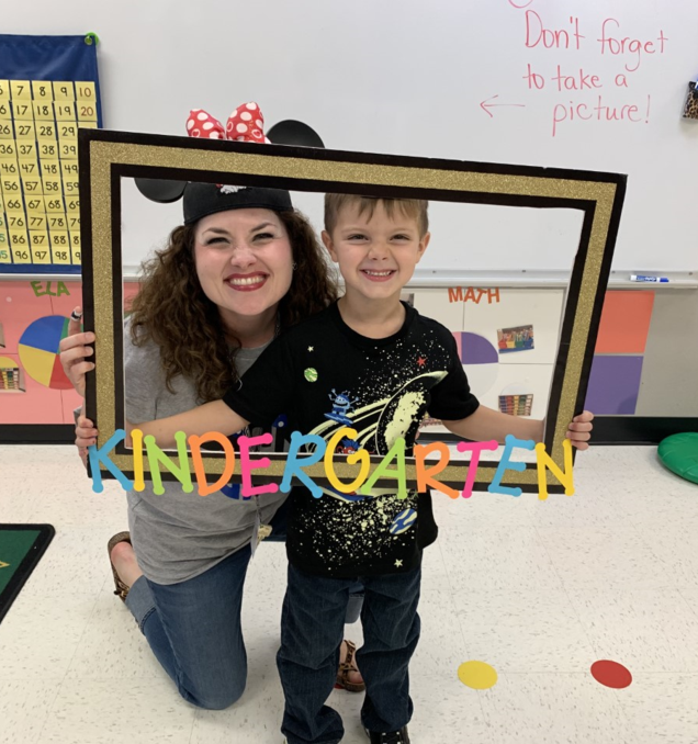 Draxton Hanson takes his picture with his teacher.