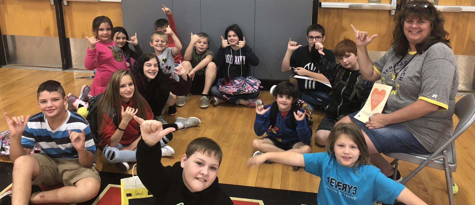 Principal sitting with a group of students