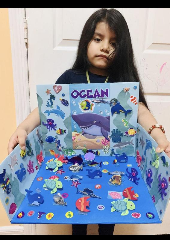 Girl standing and holding her ocean project
