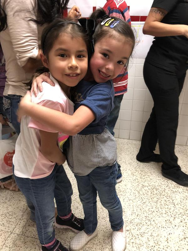 Students happy to see each other in the hallway.