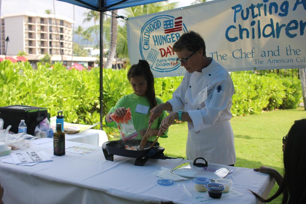 girl pouring food in a pan with chef